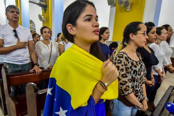 Venezolanos presionan por ayuda con rezos y agua bendita en Curazao