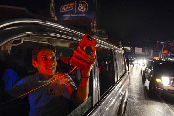 Familias enteras salen a buscar señal para sus celulares ante apagón en Venezuela