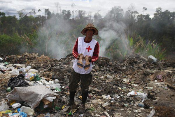 Venezolanos disputan restos de comida con buitres en un basurero en Brasil